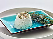 Fresh goat's cheese with herbs on a blue plate