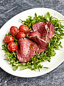 Tagliata di Manzo (beef fillet on a bed of rocket with cocktail tomatoes, Italy)