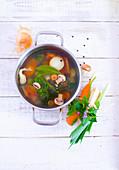 Gemüsefond im Topf, daneben ein Bund Suppengrün (Aufsicht)