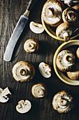Frische Champignons, ganz und geschnitten auf Holzuntergrund