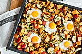 Oven-baked sweet potatoes and eggs with pepper, courgette, black beans and sweetcorn