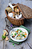 A plate of dumplings with creamy mushrooms, and a basket of freshly harvested wild mushrooms