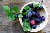 Damsons with a a twig and leaves in a wooden dish (seen from above)