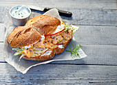 A spelt roll with salmon on sandwich paper