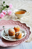Small muffins on a plate with a fork, a teacup and flowers