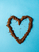Heart made with grinded coffee powder over blue background