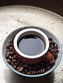 Coffee beans in a bowl and a cup of espresso on metal tray background