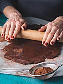 Frau rollt Teig für Schokoladenplätzchen aus