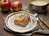 Apple strudel on a pewter plate with vanilla sauce