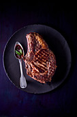 A beef chop on a black plate against a black background (top view)