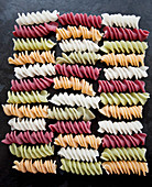 Colourful fusili pasta made from vegetables (beet, spinach), on a black countertop