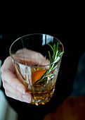 A woman in a black sweater holding a glass of bourbon with an orange slice and sprig of rosemary in it
