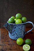 Mini limes piled in an antique blue enamel jug on a wooden tabletop