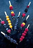 Frozen berries on wooden skewers - blackberries, raspberries, blueberries and golden berries