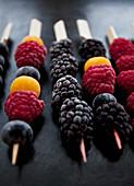 Frozen berries on wooden skewers - blackberries, raspberries, blueberries and golden berries