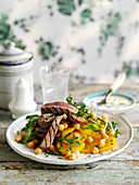 Grilled steak slices with yellow beetroot, chickpeas, and rocket