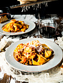 Pappardelle bolognese on rustic table grating cheese