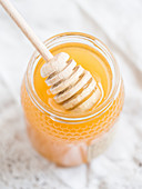 A jar of Portuguese honey with a honey dipper (close-up)