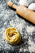 Ribbon pasta with a rolling pin on a floured work surface (top view)