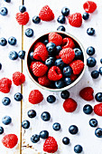 Raspberries and blueberries in a bowl against a wooden background (top view)