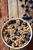 Granola mit frischen Blaubeeren im Schälchen (Aufsicht)