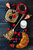 Frühstückszutaten: Müsli, Beeren, Joghurt und Croissant (Aufsicht)