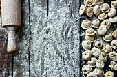 Hausgemachte Tortellini mit Nudelholz auf bemehlter Holzarbeitsfläche (Aufsicht)