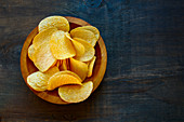 Crisps in a wooden bowl on a dark wooden surface (seen from above)