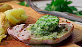 Pork steak with melting herb butter and potatoes on a wooden board