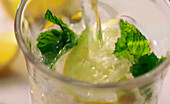 Water being pour into a glass of mint and lemon