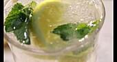 Wasser in ein Glas mit Minze und Zitrone gießen