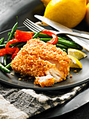 A cod fillet in a panko crust with green beans and peppers