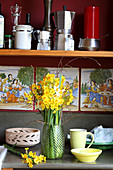 Narcissus, cream narcissus and birch twigs in vase, picture tiles and kitchen utensils on shelf