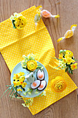 Egg-shaped sweets on bunny cake stand and spring flower in egg cups on yellow cloth