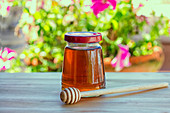 A jar of honey and a honey dipper on a garden table