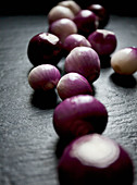 Purple and white pearl onions scattered on a black slate countertop