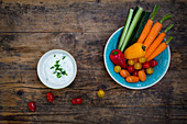 A bowl of carrots, peppers, cucumber, tomatoes and a chive dip