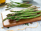 Raw green asparagus on cutting board