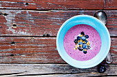 Clean eating, well being and weight loss food concept. Close up of bowl with healthy berry smoothie on rustic wooden background