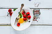 Healthy breakfast set with plate of fried egg, roasted cherry tomatoes, basil and spices on white wooden backdrop
