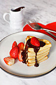 Valentine waffles with strawberries and chocolate sauce