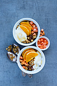 Vegetarian breakfast yogurt bowls with tasty granola, orange, dried fruit, nuts and seeds over grey background, top view