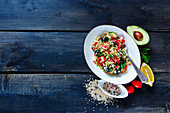 Tasty organic quinoa salad with feta cheese, cherry tomatoes, avocado, black olives in bowl on dark rustic wooden background