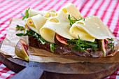 A slice of crusty bread topped with gouda, figs and rocket