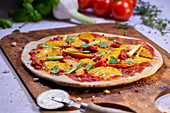 Vegetable pizza with pumpkin on a pizza paddle