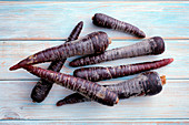 Purple carrots on a wooden background