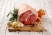Pork roasting joint with ingredients on a chopping board