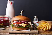 A beefburger with chips on a wooden chopping board