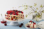 A summery layer cake with berries and cherries, sliced