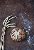 A wheat bread roll with black sesame seeds